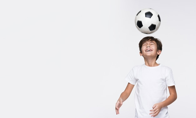 Kleiner junge spielt mit fußball