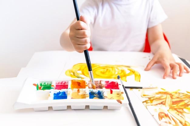 Kleiner junge spielt mit hausgemachten farben