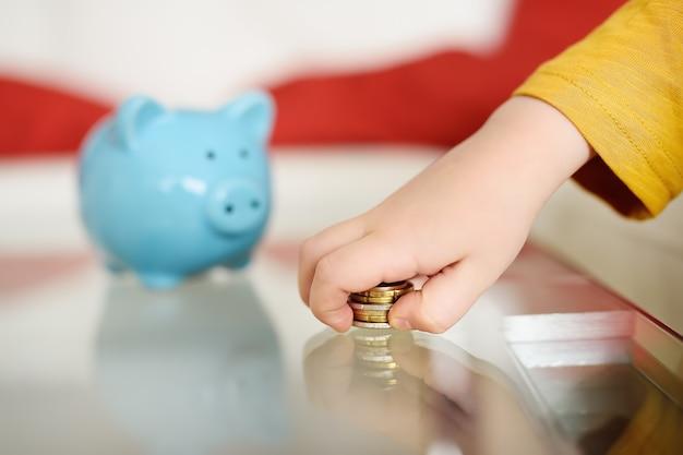 Kleiner junge spielt mit münzen und träumt von dem, was er kaufen kann. ausbildung von kindern in finanzkompetenz.