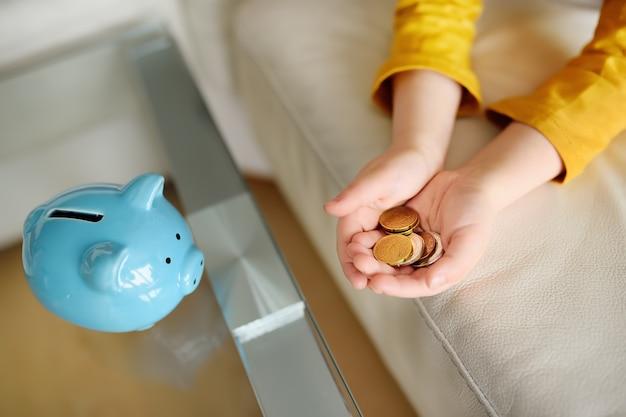 Kleiner junge spielt mit münzen und träumt von dem, was er kaufen kann.