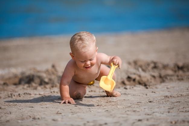 Kleiner junge spielt mit sand am meer