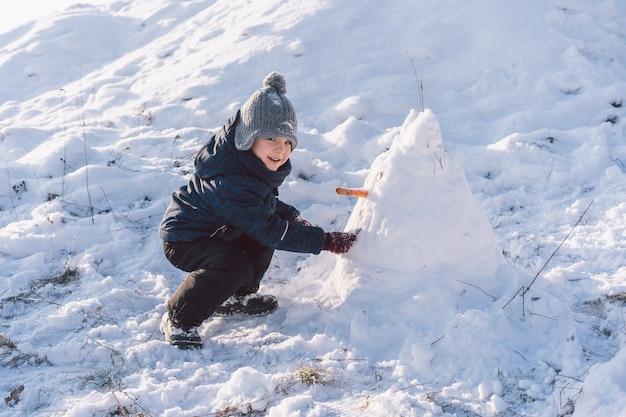 Kleiner junge spielt mit schnee