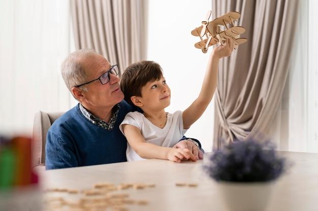 Kleiner junge spielt mit seinem großvater