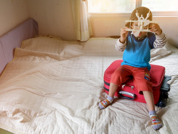 Kleiner junge spielt mit spielzeug flugzeug, reise-und abenteuer-konzept