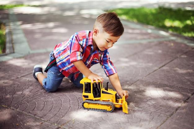 Kleiner junge spielt mit spielzeug im sommerpark