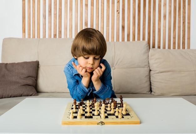 Kleiner junge spielt schach an einem tisch in einem raum