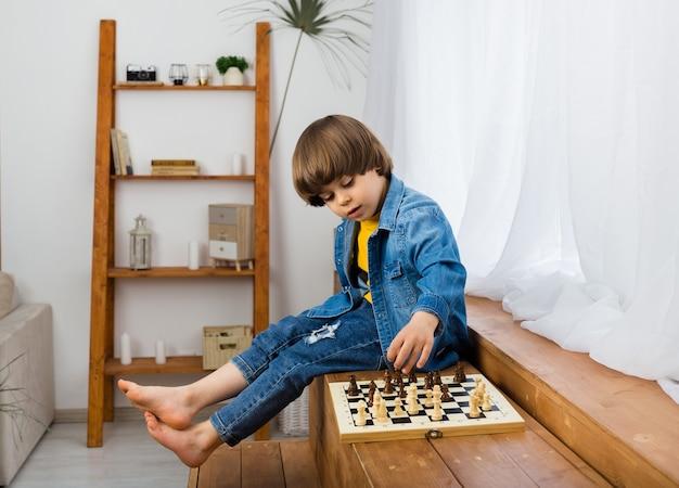 Kleiner junge spielt schach auf einem schachbrett in einem raum