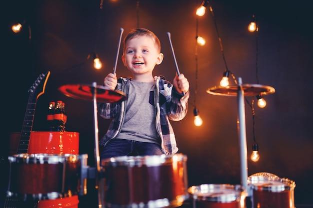 Kleiner junge spielt schlagzeug auf der bühne