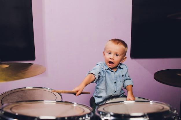 Kleiner junge spielt schlagzeug im aufnahmestudio.