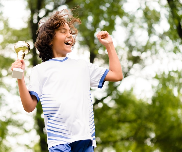 Kleiner junge springt, nachdem er ein fußballspiel gewonnen hat
