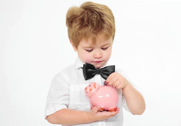 Kleiner junge steckte münze in sparschwein. geld sparen konzept. finanzen. kind mit spardose. werbung für banken.