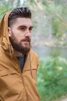 Kleiner junge trägt eine jacke mit kapuze, um sich vor dem kalten herbst zu schützen