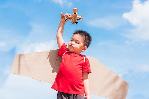 Kleiner junge trägt spielzeugflugzeugflügel und spielt mit spielzeugflugzeug