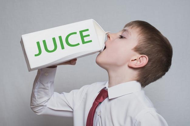 Kleiner junge trinkt aus einem großen weißen saftpaket. weißes hemd und rote krawatte. heller hintergrund.