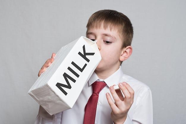 Kleiner junge trinkt aus einer großen weißen milchpackung