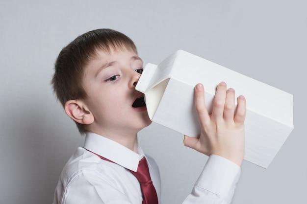 Kleiner junge trinkt aus einer großen weißen packung. weißes hemd und rote krawatte. heller hintergrund