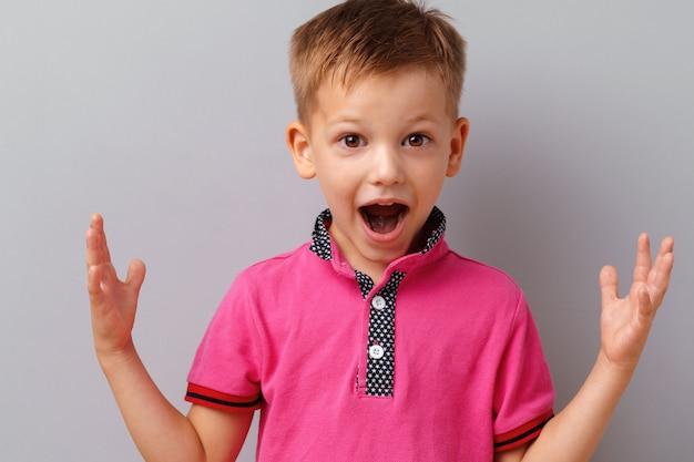 Kleiner junge überrascht und geschockt, rosa t-shirt tragend