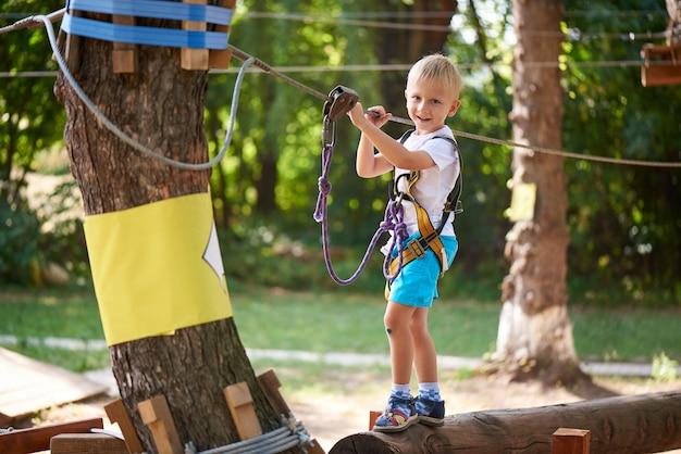 Kleiner junge überwindet das hindernis im seilpark.