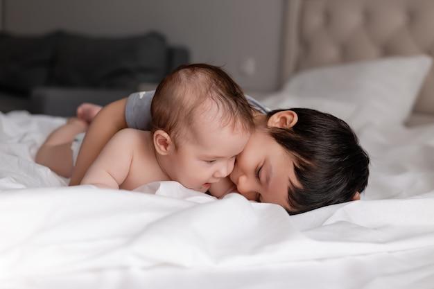 Kleiner junge und ein baby zwei brüder liegen auf weißer bettwäsche im bett und umarmen sich