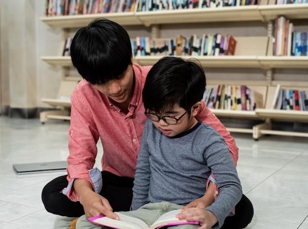 Kleiner junge und lehrer lesen zusammen buch, verschwommenes licht herum