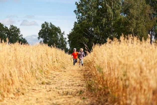 Kleiner junge und mädchen auf einem weizenfeld im sonnenlicht laufen und spielen die natur genießen. kind, das über feld- und sonnenunterganghimmelhintergrund anhebt. umweltkonzept für kinder