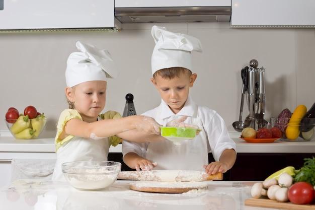 Kleiner junge und mädchen backen zusammen in der küche