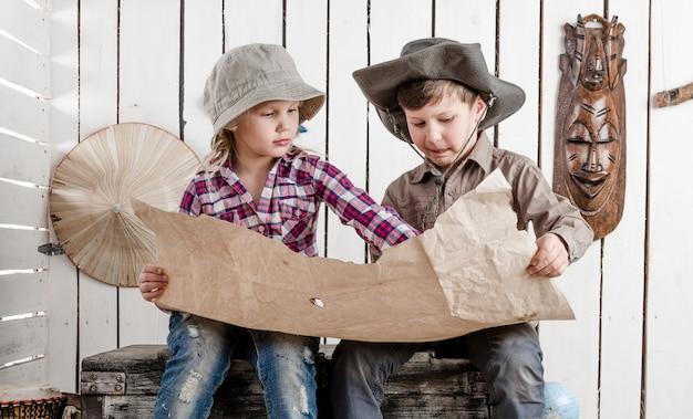 Kleiner junge und mädchen beobachten die karte