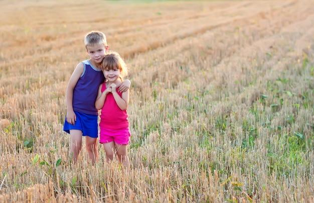Kleiner junge und mädchen, die auf feld und dem umarmen steht