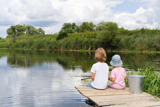 Kleiner junge und mädchen, die in einem teich fischen
