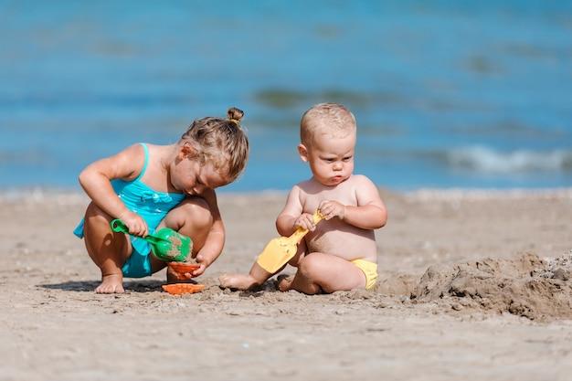 Kleiner junge und mädchen, die mit sand durch das meer spielt