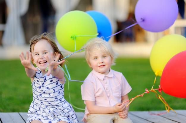 Kleiner junge und mädchen, die spaß hat und geburtstagsfeier mit bunten ballonen feiert