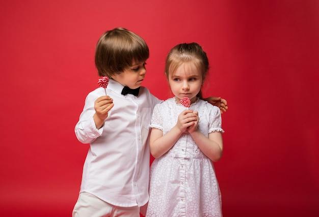 Kleiner junge und mädchen, die süßigkeiten auf stock halten und auf rot mit raum für text umarmen