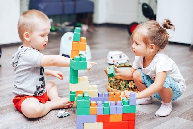 Kleiner junge und mädchen, die zu hause spielwaren spielt