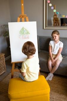Kleiner junge und mädchen, die zu hause zusammen mit der staffelei zeichnen