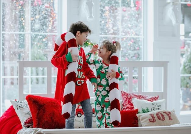 Kleiner junge und mädchen im weihnachtspyjama, die auf weißem bett mit weihnachtskissen gegen großes weißes fenster stehen.