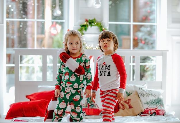 Kleiner junge und mädchen im weihnachtspyjama, die auf weißem bett stehen