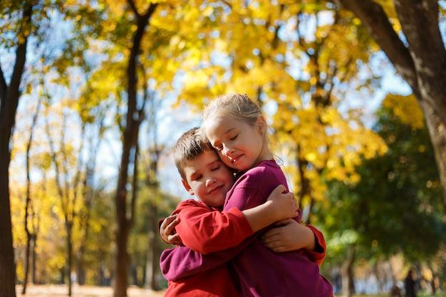 Kleiner junge und mädchen in einem park im herbst. junge, der ein mädchen umarmt