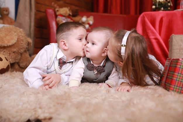 Kleiner junge und mädchen küssen ihren kleinen bruder und liegen in der nähe eines weihnachtsbaumgeschenks. neujahr. familie, glück, feiertage, weihnachtskonzept.