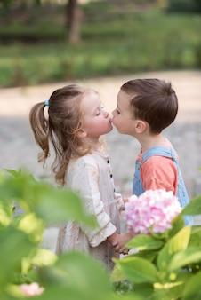 Kleiner junge und mädchen stehen händchen haltend und küssen valentinstag