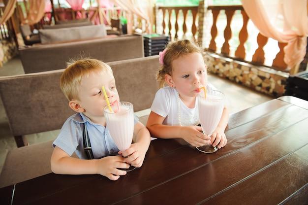 Kleiner junge und mädchen trinken milchshakes in einem café im freien.