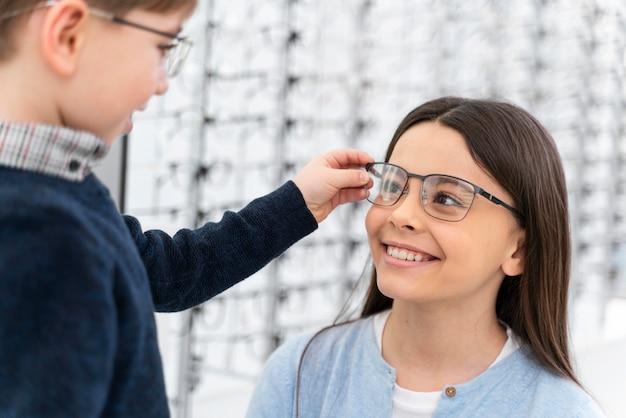 Kleiner junge und schwester im laden, die brille anprobieren