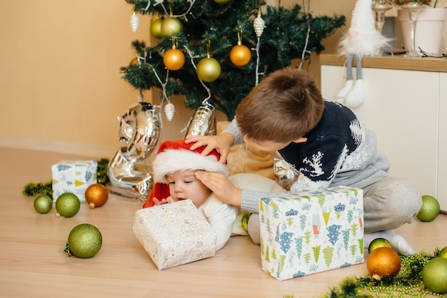 Kleiner junge und sein bruder spielen mit geschenken unter einem festlichen weihnachtsbaum