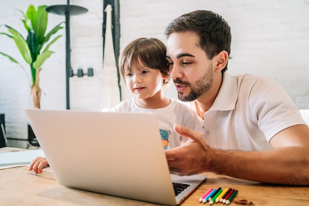 Kleiner junge und sein vater, die zusammen einen laptop benutzen, während sie zu hause bleiben. neuer normaler lebensstil. monoparentales konzept.