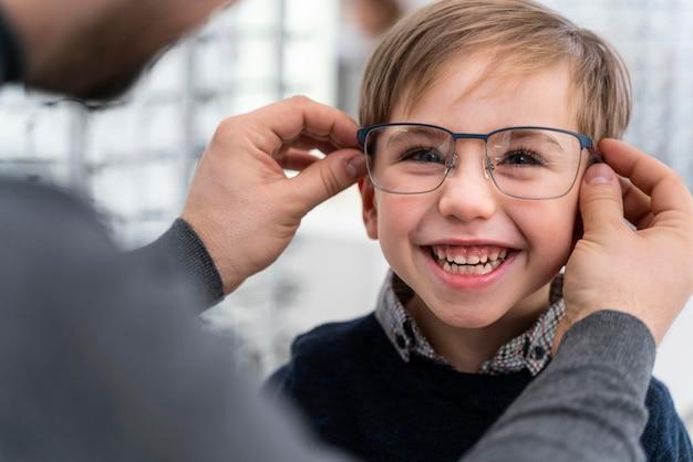Kleiner junge und vater im laden, die brille anprobieren