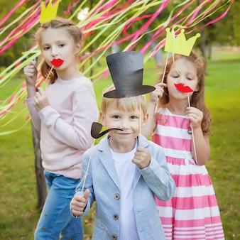 Kleiner junge und zwei mädchen, die mit papiermasken auf einer geburtstagsfeier aufwerfen