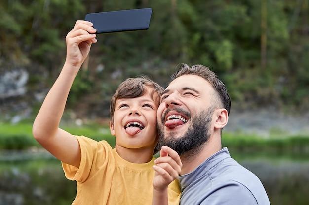Kleiner junge ungefähr 8 jahre alt und sein vater machen gesichter, während sie fotos auf dem handy am flussufer machen.