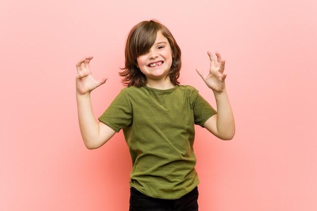 Kleiner junge verärgert mit angespannten händen schreien.
