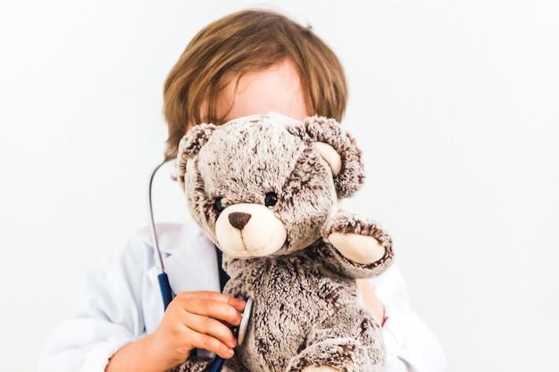 Kleiner junge verkleidet als doktor, der teddybär auf weißem hintergrund auskultiert
