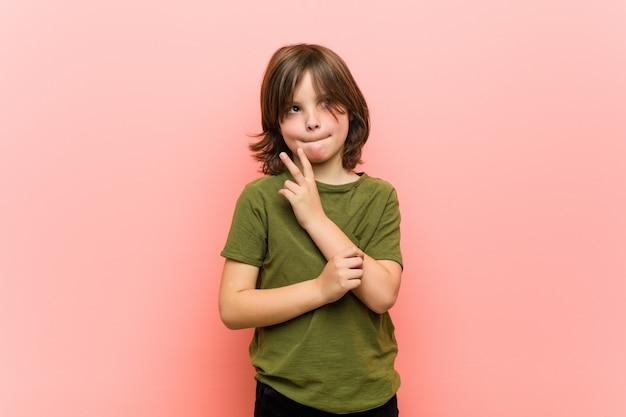 Kleiner junge verwirrt, fühlt sich zweifelhaft und unsicher.