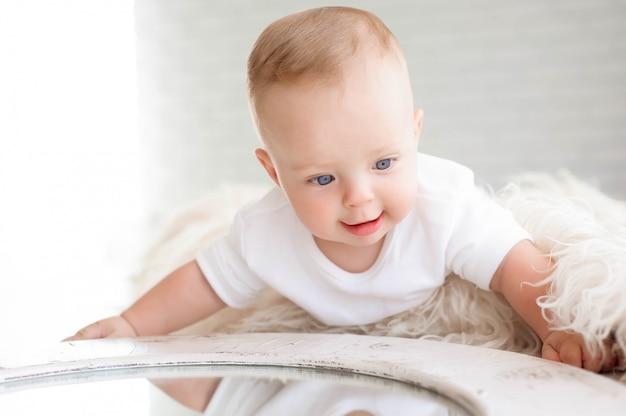 Kleiner junge von 7 monaten spielt auf dem weißen teppich im schlafzimmer